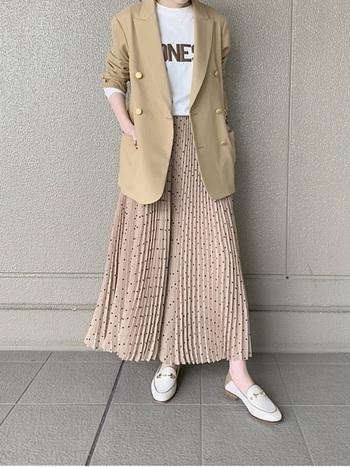 テーラードジャケット×プリーツスカートのきれいめコーデ。白のローファーが爽やかで、靴の金具とジャケットのボタンのゴールドがさり気なくリンクした大人の洗練スタイルです。