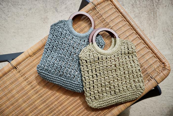 丸いウッドハンドルがアイコニックな、編み地デザイントートバッグ。落ち着いたカラーリングで、大人カジュアルの装いを格上げしてくれるアイテムです。クラッチバッグのように折りたたんで持っても◎。