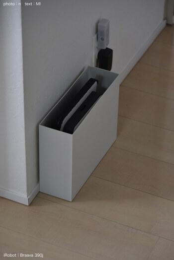こちらのファイルボックスに入っているのは、なんとロボット掃除機です。  ファイルボックスの片面に開いている、指を引っ掛けられる穴を利用して、コードを通し充電できるようにされているのだそう。  Wi-Fi機器やタブレット置き場として、コンセント周りの目隠しにも使えるアイデアですね。
