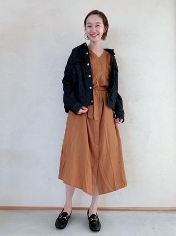 テラコッタカラーのワンピースに、ブラックデニムジャケットを抜き襟ぎみに羽織ったスタイル。アウターのボタンやビットローファーの金具など、パーツ使いのアクセントが効いています。