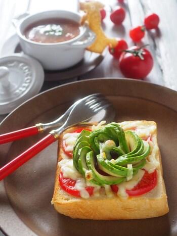 シンプルなトマトとアボカドのトーストも、アボカドの盛りつけを変えるとおしゃれな見た目に。スライスしたアボカドを丸めていくとお花のようになります。まるでカフェで出てくるような一品に。