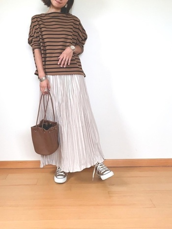 ブラウンの大人っぽいボーダーは、ブラウン系のバッグとスニーカーで揃えて統一感を。光沢のあるプリーツスカートで女性らしさを強化しましょう。