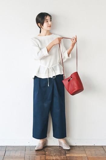 ネイビーのラップパンツに、白トップスを合わせたベーシックなスタイリング。白×ネイビーは合わせるだけで大人っぽさと爽やかさを演出できる鉄板カラーです。深みのある赤系のショルダーバッグで、着こなしがシンプルになり過ぎないようワンアクセントをプラス。