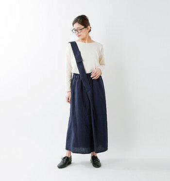 ネイビーのワンショルダースカートに、白のトップスを合わせた着こなし。白×ネイビーのベーシックなカラーリングですが、クセのあるアイテム選びでシンプルになり過ぎないコーディネートにまとめています。足元は黒シューズできちんと感をプラスして、大人の遊び心をさりげなくプラスしたスタイリングです。