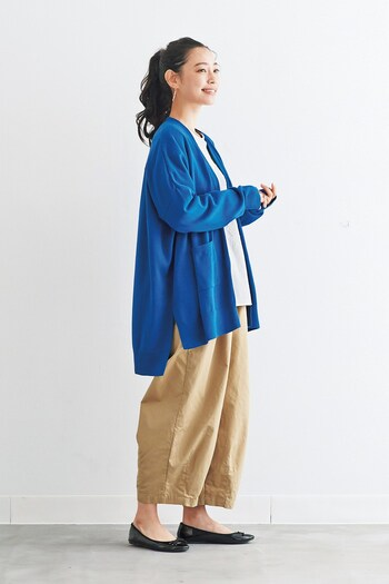 ベージュのワイドパンツに、白トップスとブルーのカーディガンを合わせた爽やかな印象の着こなし。黒のフラットシューズで、ナチュラル×カジュアルなコーディネートにまとめています。キレイめカラーのブルーが、ベージュとも好相性◎。