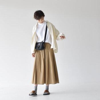 ベージュのフレアスカートに、白トップスとジャケットを合わせたカジュアルなコーディネートです。ショルダーバッグを黒にして、引き締めポイントをプラス。サンダルと靴下の組み合わせで、程よい抜け感とトレンド感をアピールしています。