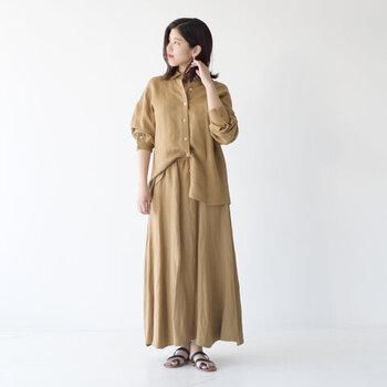 ベージュのロングスカートに、同色のシャツを合わせたセットアップ風のキレイめコーデ。シャツの左右でインとアウトを変えてアクセントをプラスしています。全部インやアウトなど、タックインの仕方でも雰囲気がガラリと変わるのがポイント。足元はサンダルで、涼しげな雰囲気を演出しています。