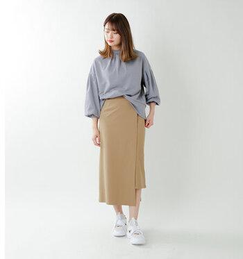 ベージュのラップスカートに、くすみブルー系のブラウスをタックインしたキレイめコーデ。通勤スタイルにも使えるきちんと感のあるスタイリングですが、あえて足元は白のスニーカーで上手にカジュアルダウンしています。シューズをパンプスに変えれば、オフィスカジュアルとしても◎。