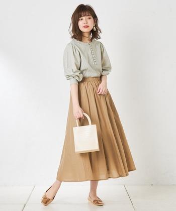ベージュのフレアスカートに、薄いグリーンカラーのブラウスを合わせたコーディネートです。さりげなく柄の入ったトップスは、ベージュボトムスとの相性も抜群。ゴールドのパンプスと白のハンドバッグで、大人感あふれるキレイめコーデに仕上げています。