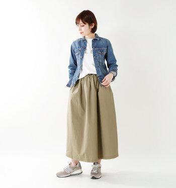 Gジャンに、ベージュのフレアスカートと白Tシャツを合わせた着こなしです。足元はスカートとカラーを合わせたスニーカーで、カジュアルに。ちょっぴりメンズライクなアイテム同士の組み合わせでも、ボトムスをスカートにするだけで、程よく大人っぽい雰囲気を演出できます。