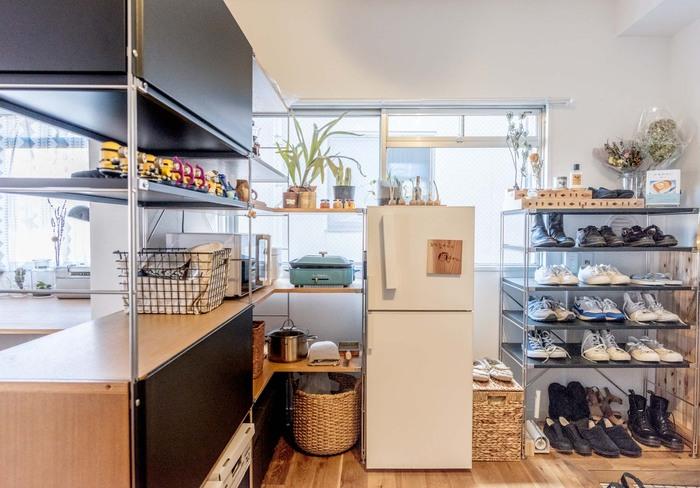 部屋のコーナーに沿って置かれたコの字型のシェルフが家電置き場になっています。 電子レンジやホットプレートなど、余白を持って整然と配置することで、ショールームのような清潔感があります。壁に沿って冷蔵庫やシューズラックも同じライン上に並べられ、すっきりとした空間に。