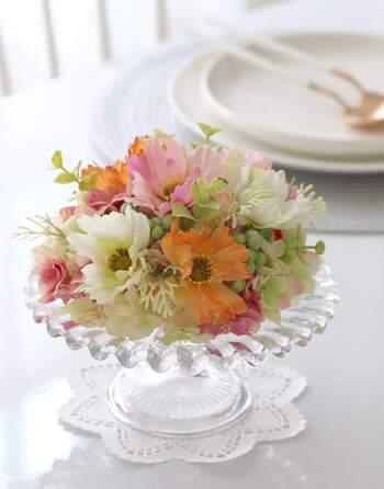 コスモスの造花をガラスのコンポート皿の上に飾って。透明な器に光が反射しフェイクフラワーの色合いを引き立てます。こんもりとボリュームを持たせるのがポイント!テーブルを華やかに演出してくれます。