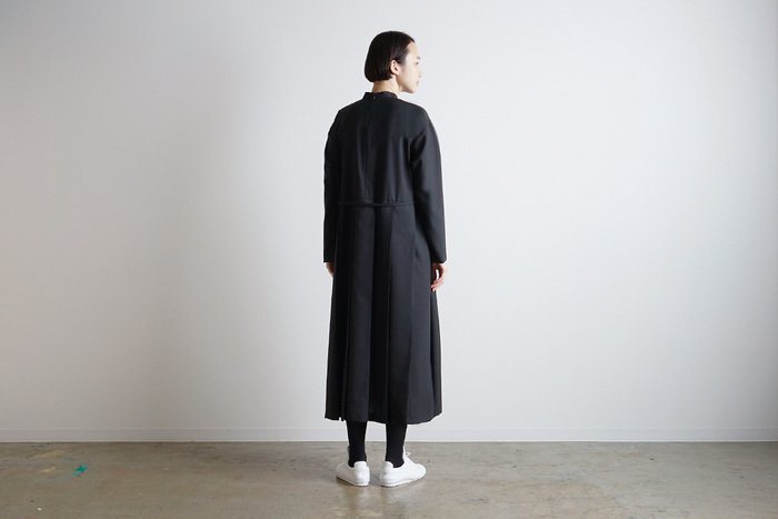 スカートの後ろ側だけにプリーツがあしらわれた、プチハイネックドレス。スーツにも使われているという上質なウール100%の生地で作られたこんなブラックドレスは、どんな場面でも活躍してくれる頼もしい存在になってくれそう。