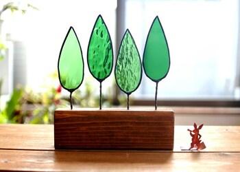 ステンドグラスで森を表現した置き物。木の形をしたグリーンのステンドグラスで土台はメープル仕上げ。窓際など日が当たる場所に飾ると、ステンドグラスの美しさがより引き立ちます。