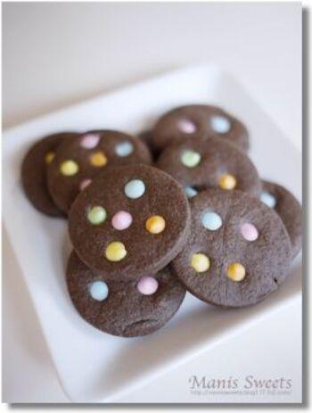 丸く型抜きしたクッキーにストローで数ヵ所穴をあけて焼き上げ、仕上げに固まるタイプのチョコペンを穴に絞り出すだけ!数色使うとマーブルチョコのようなポップな仕上がりに。ココア生地にすることで、デコレーションのカラフルさがより引き立ちますね。