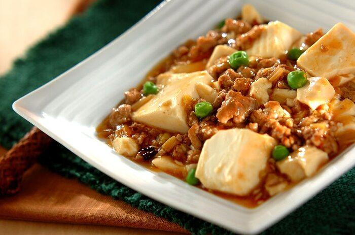 市販の麻婆豆腐の素を使わず、豆腐と豚ひき肉、白ネギ、ショウガ、ニンニク、豆板醤や  顆粒チキンスープの素などの調味料で作る本格的な麻婆豆腐。ニンニクとショウガの香りが食欲をそそり、豆板醤のピリッとした辛さはまるでお店でいただくような仕上がりに。お手ごろ価格の材料で、美味しく作れるのも嬉しいポイントです。