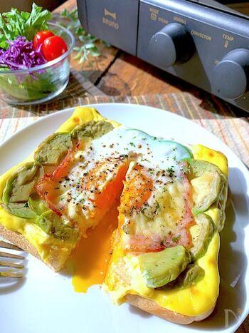 休日のランチにもぴったりなカルボナーラ風のアボカドトースト。マヨネーズを食パンの縁にぐるりとかけて具材を並べ、卵を落として焼きます。トロッと卵が食欲そそるレシピです。