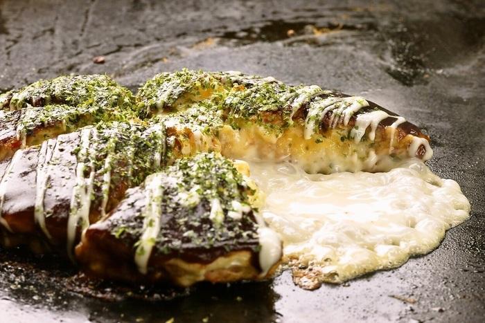 昭和25年創業の老舗お好み焼き店。地元の人からも観光客からも長く愛され続けてきた名店です。店員さんが焼いてくれるので、お好み焼きに慣れていない人でも安心です。 こちらはフロマージュ焼き。ゴーダ・チェダー・モッツァレラなど5種のチーズが使われていて、メディアでもよく取り上げられる人気メニュー♪