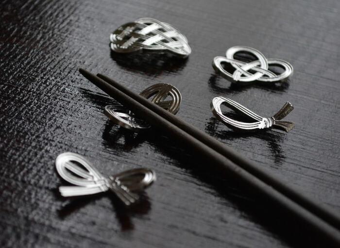 水引の結びをモチーフにして作られた能作の箸置き。抗菌性やサビに強いため、安心して使えます。能作の錫は純度100%なので、簡単に曲げられます。日本らしい縁起のいい形と錫の高級感で食卓がワンランクアップしそうですね。