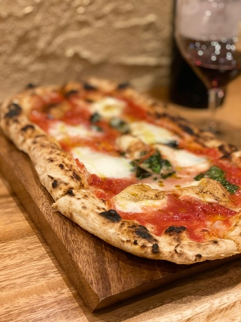 「ドットリーノ」のピザは四角い形。メニューも豊富で、燻製されたモッツアレラが乗った「ブファリーナ」は、シンプルなトマトソースにバジル、そして燻された香りを放つ濃厚なモッツアレラが乗っていてその相性は抜群!ワインのお供にぴったりです。  ※筆者撮影
