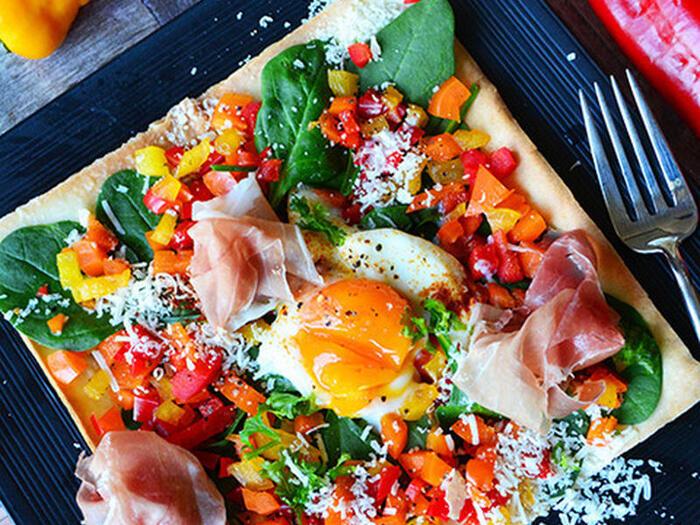 春巻きの皮を使った楽しいピザです。春巻きの皮にパルミジャーノ・レッジャーをミルフィーユしてトースターでこんがり焼いたら、野菜と生ハム、卵を好きなようにトッピング♪オシャレな見た目で、家族も喜んでくれそうですね。