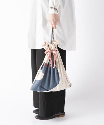 しっとりとした質感で、光沢のある生地を採用した大きめの巾着バッグです。上品さを感じさせる総柄デザインは、さまざまなスタイリングに合わせやすいのが魅力。開き口を絞らずに使えば、トートバッグとしても活用できます。