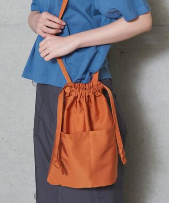 綿ナイロン素材を採用し、カジュアルなデザインながら上品なツヤ感のある巾着バッグです。カジュアルコーデに合わせてラフにスタイリングしても、あえてフェミニンなコーデのハズシアイテムとして活用してもOK。持ち歩きに必要なものは、ある程度入る程よいサイズ感も魅力です。