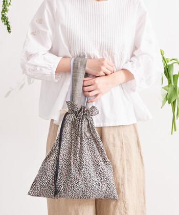 パッチワークのように、生地をつないで作られた総柄の巾着バッグ。持ち手の部分は取り外しも可能なので、大きめの巾着としても活用できるのが特徴です。裏側はシンプルなレース生地なので、持つ向きを変えるだけでコーデの雰囲気をガラリと変えられるのもポイント♪