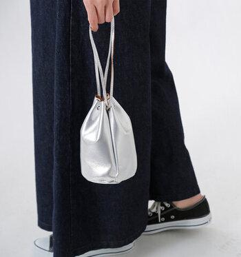 薄くて柔らかい山羊革を採用し、使い込むほどに馴染んでいく風合いが魅力の巾着バッグです。小ぶりなサイズ感ながら、しっかりとマチがあるので必要最低限の荷物を持ち歩きたいときにもぴったり。ゴールドとシルバーの2色展開で、シンプルコーデに合わせるのもおすすめです。