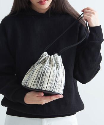 白黒ラメのツイード風ボーダー生地で作られた、モノトーンデザインの巾着バッグです小ぶりなサイズ感と肩に掛けられる長さのストラップで、合わせるスタイルを選ばないアイテムに。シンプルなカラーリングの巾着バッグなので、どんなカラーリングのアイテムとも馴染みやすいのが魅力です。