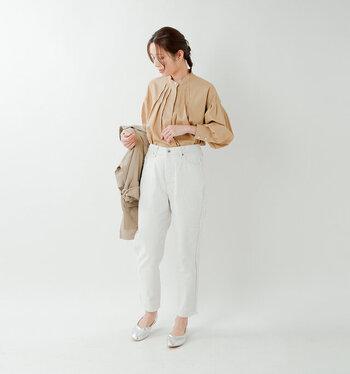 白のテーパードデニムに、ベージュのブラウスを合わせたコーディネート。裾をきっちりとタックインして、きちんと感のある着こなしにまとめています。足元はシルバーのパンプスで、ベーシックコーデにワンアクセントをプラス。オフィスカジュアルとしても使える、キレイめスタイルです。