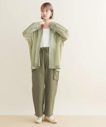 透け感のあるグリーンのシャツに、カーキカラーのワイドパンツを合わせた同系色コーデ。インナーはシンプルに白をチョイスして、前を開けても閉めてもOKのフェミニンスタイルにまとめています。シューズも白で揃えて、季節感のある着こなしに。