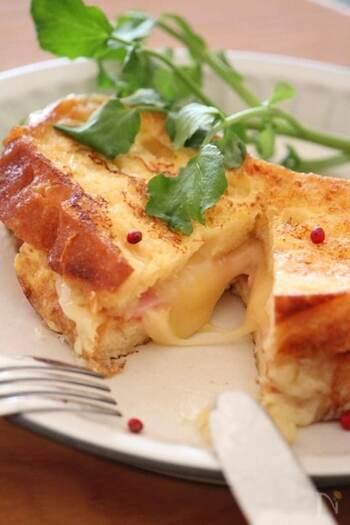 フライパンで作る、フレンチトーストのホットサンドです♪漬け込み液に砂糖は入れず、卵と牛乳、塩のみで作ります。  焼きながら、ハムやチーズをサンドしていきます。チーズが溶けたら完成。ナイフで切ったときにとろ~りとろけて、見た目もとってもおいしそうです!バゲット以外に、食パンでもできますよ。
