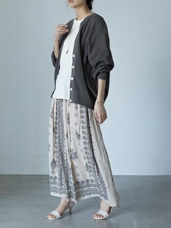 エスニックな柄のスカートには、チャコールグレーの大きめカーデを合わせて。主張しないホワイトのサンダルとインナーをリンクさせ、統一感を。