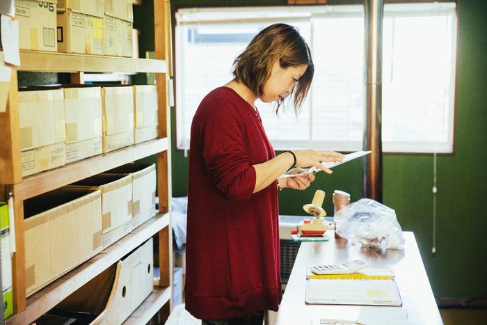 専務取締役・千葉弘美さん。内職のお針子さんに送る指示書と材料を確認中。それぞれ得意分野があるため、アイテムの特性を見極めながら発注する