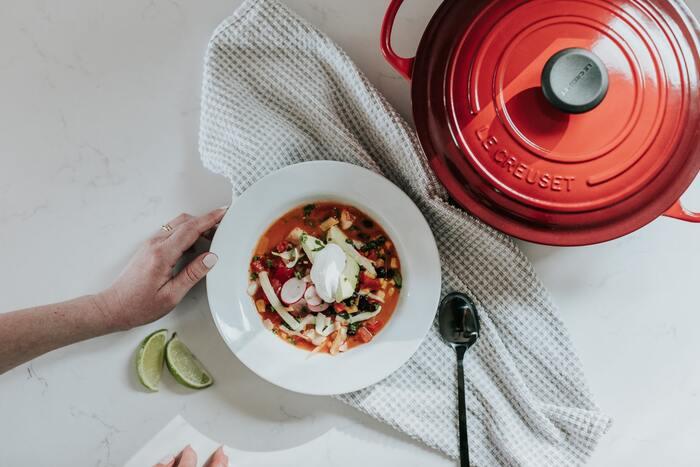 ル・クルーゼの鍋は、熱が温度の高いところから低いところに移動する「熱伝導」と、熱を蓄える「蓄熱性」に優れています。食材にゆっくりと「均一に火を通す」ことができ、煮崩れを防いで素材の甘さなどをより引き出してくれるんですよ。  また、「スチームコントロール機能」によってバランス良く蒸気を逃がして同時に雑味も取り除き、旨味を引き出してくれることもポイント。つまり、おいしさと栄養をぎゅっと閉じ込めたいお料理作りにぴったりなんです。
