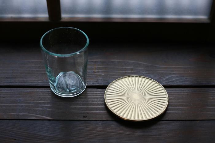 真鍮の生活用品ブランド「FUTAGAMI」の真鍮鋳肌のコースター「光芒(こうぼう)」。アイテム名通り、光の筋をモチーフとした気品あふれるコースターは見た目の美しさだけでなく、機能性もバッチリ。グラスの底に付いた水滴を筋状に分散してくれるので、グラスにコースターが貼りつかず快適に使えます。