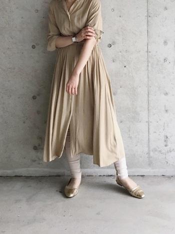 ベージュのシャツワンピースに、ゴールドのフラットシューズを合わせて統一感を。レギンスはさりげなくアイボリーにすることでコーデに自然な立体感を作ります。