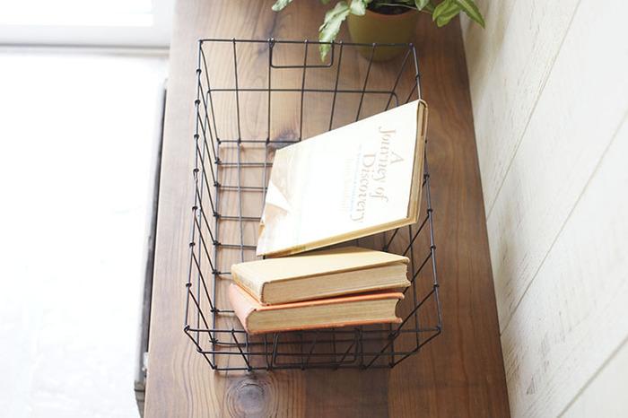 かごタイプの収納アイテムも本を入れてステキなインテリアに。ワイヤータイプのシンプルなデザインで、シェルフの上やベッドの横などどんな場所にも似合いますよ。四角い形だと本を並べて多く収納できるし、持ち手があるから移動もしやすいですね。使わない時には他のものを入れて置けるのも便利です。