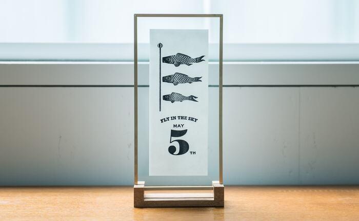 ヴィンテージの活版印刷機でハンドプリントした鯉のぼりのポスター。こちらは真鍮のフレームとオーク材のスタンドがセットになっています。中のポスターはもちろん取り外し可能。また壁掛けにもできます。季節感のあるものはインテリアに取り入れやすいのでおすすめです。