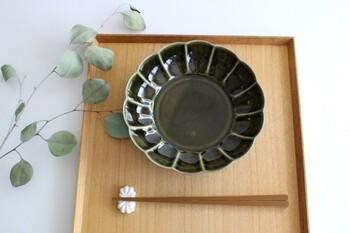 深みのあるオリーブグリーンと釉薬の濃淡が美しい皓洋窯の「菊割平鉢」。ぽってりとした菊の花のモチーフと艶感があたたかい雰囲気です。みぞれ煮や煮つけを盛り付けるだけで品のある食卓を演出できそうですね。