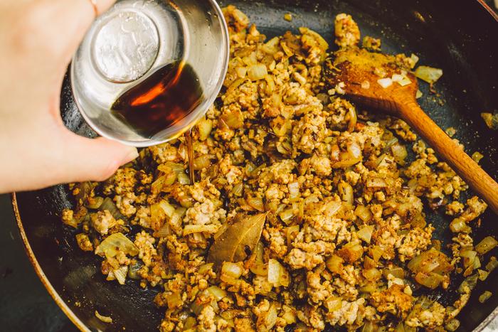 全体の粉っぽさがなくなったら、調味料(酒・醤油・ナンプラー)を加えます。