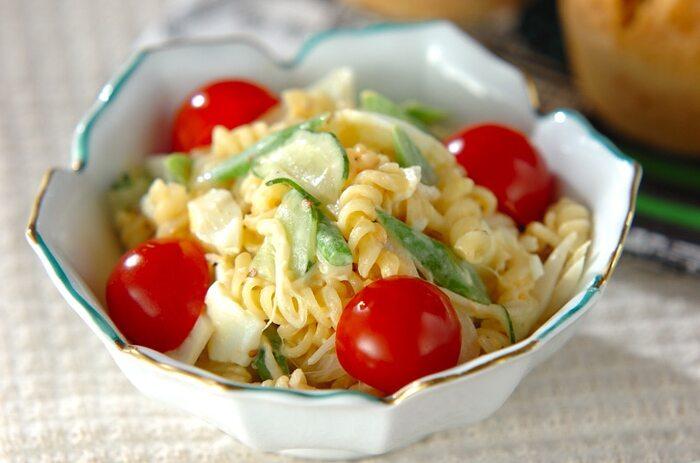 マカロニサラダは、おかずが少し物足りないときに添えると、お腹も満たしてくれる便利なグルメです。こちらは、サヤインゲン、キュウリ、プチトマトなど彩り豊かな具材のレシピ。サヤインゲンはマカロニと同じくらいの長さに切るのがポイントです。マヨネーズと粒マスタードを合わせた定番の味わい!