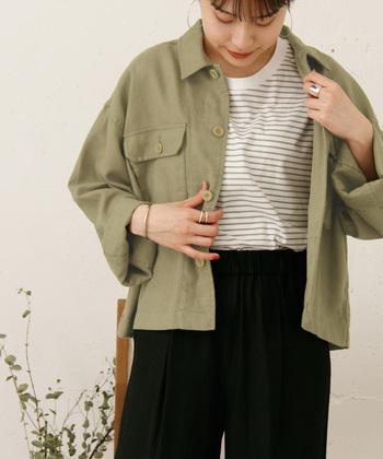 シンプルなミリタリージャケットには、インナーはボーダーTシャツ+ボトムは太めの黒パンツでまとめて。女性らしいニュアンスはアクセサリーやネイルでプラスしましょう。