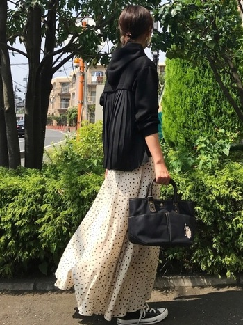 ベージュのドットスカートなら柔らかな印象に。フレアなマキシスカートなので、黒のパーカーとスニーカーでカジュアルにまとめても女性らしいシルエットを崩しません。