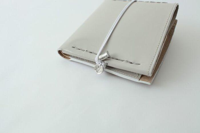 ガラスレザーという名のとおり、エナメルを思わせる上品な艶、くるりと巻かれたゴムの先に輝くシルバーチャーム。デザイナー曽我部 美加さんの世界観は、小さなお財布にも現れています。まるで雑貨屋さんのショーケースに置いてありそうな可憐な二つ折り財布です。