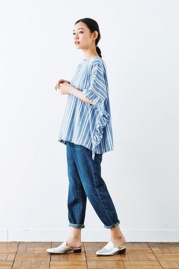 ポンチョ風のトップスはベーシックなジーンズと合わせてシンプルにコーディネートするのがおすすめ。ロールアップすると足元がすっきりしてスタイルアップ効果も。メタリック調のシューズを履いて、足元にポイントを置くのもアリ。