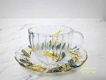 ガラスのカップ&ソーサーにミモザを散りばめた春らしさ。心穏やかにティータイムを過ごせそうなボタニカルなデザインです。