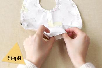 表地と裏地を型紙通りにカットしたら、布の表同士を合わせて、周囲をぐるりと縫っていきます。首回りのカーブがきついところは、ぬいしろ部分に切り込みを入れて、ごろごろしないようにします。  返し口を残して縫い終わったら、返し口から表側に布地を返します。