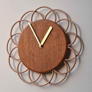 YARNのマホガニーと革紐で作られた「掛け時計」。花びらを描いた革紐のデザインは機能も考えられた配置で、根元で時間がわかるようになっています。温もりを感じるナチュラルな木板と真鍮の針の組み合わせが素敵。サイズは、大小あります。